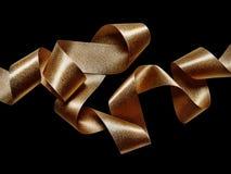 Gold bronze metallic ribbon on black Stock Photo