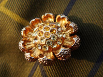 Gold Brooch with Rhinestones. Sparkling, golden flower brooch with inlaid rhinestones on plaid fabric Stock Photos