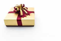 Gold and brown gift box with ribbon bow. Royalty Free Stock Photos