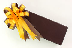Gold and brown ribbon bow with giftbox on white background Royalty Free Stock Photos