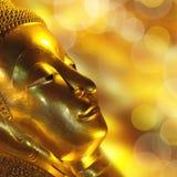 Gold Buddha face. Golden bokeh background Royalty Free Stock Photos