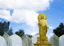 Gold Buddha in front of Blue Sky. Golden Buddha standing tall with the blue sky and some clouds in the background Stock Photo