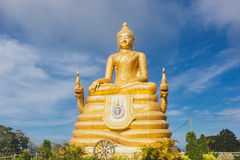 Gold Buddha Image with blue sky and scattering cloud. Royalty Free Stock Photos