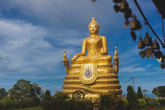 Gold Buddha Image with blue sky and scattering cloud. Royalty Free Stock Photography