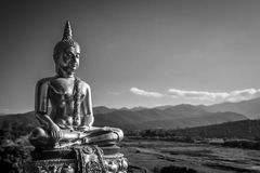 Gold Buddha Statue. Black and white photography of gold buddha statue in lotus position with mountain background Royalty Free Stock Photography