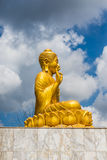 Gold Buddha Statue on blue sky background Royalty Free Stock Photos