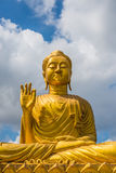Gold Buddha Statue on blue sky background Stock Images