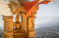 Gold buddha statue in golden recess with buddhist white and orange flags and mountain background Royalty Free Stock Images