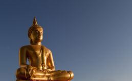 Gold Buddha Statue. In lotus position with blue dark sky background Royalty Free Stock Photo