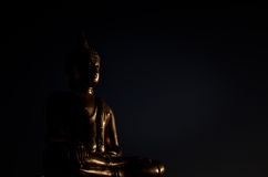 Gold Buddha Statue. In lotus position with chiaroscuro and dark background Stock Image