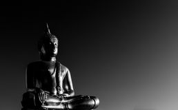 Gold Buddha Statue. In lotus position with dark background and chiaroscuro Royalty Free Stock Images
