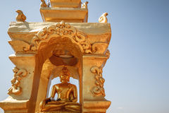 Gold Buddha statue in lotus position meditating inside golden recess Stock Photos