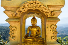 Gold Buddha statue in lotus position meditating inside golden recess Royalty Free Stock Photography
