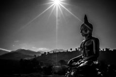 Gold Buddha Statue. In lotus position with mountain background iand sunlight n Thailand Royalty Free Stock Photo