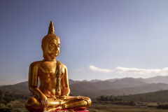 Gold Buddha Statue. In lotus position with mountain background in Thailand Stock Images