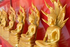 Gold Buddha Statue with a naga over head Stock Photo