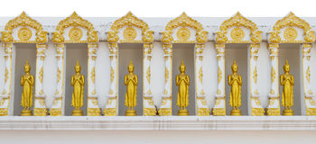 Gold Buddha statue stand up on white wall at temple. Stock Photography