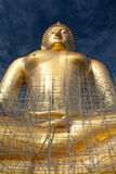 Gold buddha statue under construction in Thai temple with clear sky.WAT MUANG, Ang Thong, THAILAND. Large gold buddha statue is under construction in 2011 at Stock Image