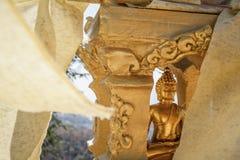 Gold-Buddha-Statue versteckt in weniger goldener Pause mit buddhistischer weißer wellenartig bewegender und fliegender Flagge Stockfotos