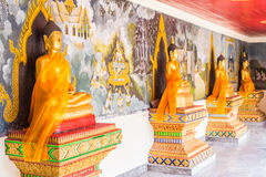 Gold Buddha statue and wall-art depicting ancient Royalty Free Stock Image