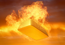 Gold Bullion on Fire. Gold bullion in a fire on a colored background of the sky Royalty Free Stock Image