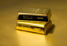 Gold bullion on golden Stock Photos