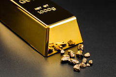 Gold bullion and nuggets. On a dark background Stock Photos