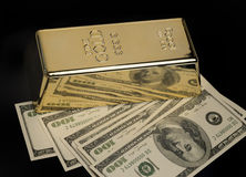 Gold bullion and US Dollar currency Stock Photography