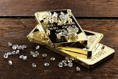 Gold bullions with diamonds. Gold bullions and diamonds on wooden background royalty free stock photography
