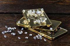 Gold bullions with diamonds. Gold bullions and diamonds on wooden background stock photo