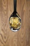 Gold bullions on spoon Stock Photos