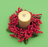 Gold candle in circleof red artificial berries Stock Images