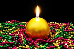 Gold candle and colourful beads. Royalty Free Stock Photography