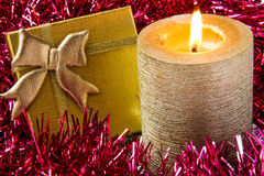 Gold candle with gift. And red tinsel Stock Photos
