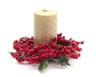 Gold candle surrounded by red berries Royalty Free Stock Photography