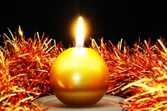 Gold candle and tinsel. Stock Photos