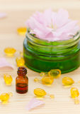 Gold capsules of natural cosmetik for face, a little bottle with essential oil and rose on the wooden Stock Photo