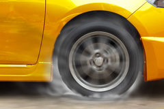 Gold car racing spinning wheel burns rubber on floor. Royalty Free Stock Images