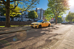 Gold car in the street of Rotterdam. Gold   the street of Rotterdam. City channels. Street along the canal. Trees and cars along the canal  sunny weather Stock Photos