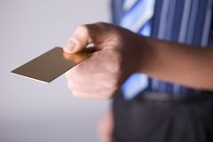 Gold card. Man's hand holding gold credit card. Focus on the card. Body unfocus Stock Photography