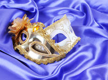 Gold carnival masks on blue silk fabric Royalty Free Stock Photo