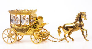 Gold carriage. The gold carriage with a horse  decorated with shining transparent crystals Royalty Free Stock Photo