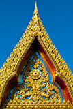 Gold carved on the ancient church. Gold carved at the front of ancient church with in blue sky stock photo