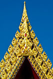 Gold carved on top of ancient church. With a beautiful day in Bangkok Thailand Stock Image