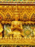 Gold carvings of celestial deities on the walls of kings palace Bangkok. Gold carvings of celestial deities on the walls of kings palace Royalty Free Stock Photography