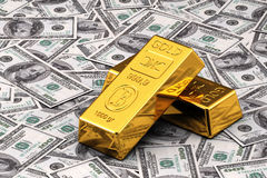Gold and Cash. Two gold bullions on hundred Dollar bills Stock Images