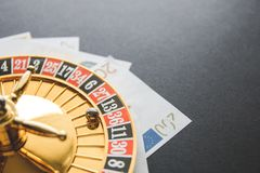 Gold casino theme. Image of casino roulette, poker games, money on the table, all on a dark bokeh background. Place for printing. And logo royalty free stock image