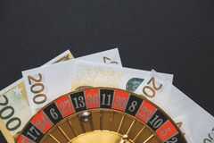 Gold casino theme. Image of casino roulette, poker games, money on the table, all on a dark bokeh background. Place for printing. And logo stock photos