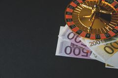 Gold casino theme. Image of casino roulette, poker games, money on the table, all on a dark bokeh background. Place for printing. And logo royalty free stock photography