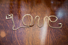 Gold chain arranged in form of word Love stock images